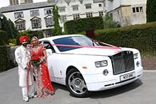 Newly wedded Asian couple beside Rolls Royce wedding car at Coombe Abbey