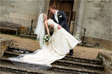 Groom holding Bride on chapel steps at Walton Hall, Stratford-upon-Avon