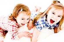 Two lively, smiling kids on a bean bag in our photography studio